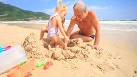 Замок песка строения детей Grandpa на пляже прибоем волны сток-видео