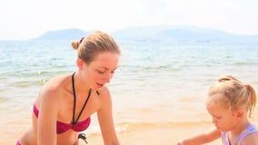 Замок песка строения дочери матери маленький на пляже лазурного моря сток-видео