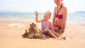 Замок песка строения дочери матери маленький на пляже лазурного моря видеоматериал