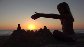 Замок ребенка строя на пляже на заходе солнца, ребенк играя пески на взморье, море девушки сток-видео