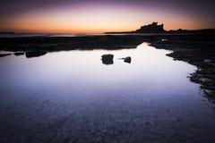 Замок Bamburgh в Нортумберленде увиденном через rockpools на зоре Стоковые Изображения