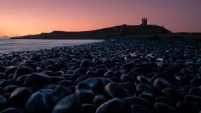 Замок Dunstanburgh увиденный от моря Стоковые Изображения RF
