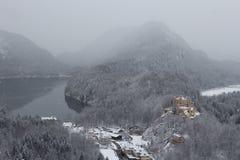 Замок Hohenschwangau, озеро Alpsee на левой стороне и Schwanensee на праве с Альпами на предпосылке Баварии Германия Стоковое фото RF