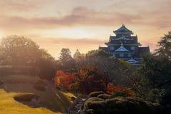 Замок Oakayama пока заход солнца в Японии стоковое фото rf