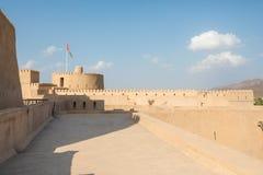 Замок Rustaq с оманским флагом на солнечный день стоковая фотография
