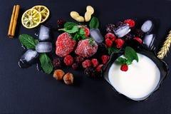 Замороженная поленика, ежевика, клубники, листья мяты плиты югурта, части льда на черном сланце всходит на борт, куски лимона, га стоковые изображения rf