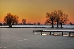Замороженное озеро во время захода солнца Стоковое Изображение RF
