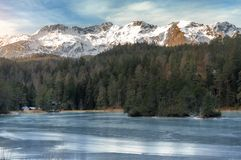 Замороженное озеро и снег-покрытые горы Стоковое Фото