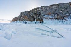 Замороженное озеро Biakal в Сибире, России Треснутый лед на поле снега с горой в зиме Стоковая Фотография RF