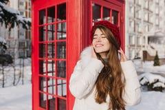 Замороженное солнечное утро снега жизнерадостной молодой женщины с длинными волосами брюнета в красной шляпе наслаждаясь зимним в стоковая фотография rf