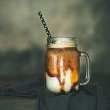 Замороженное macciato карамельки с молоком в стеклянном опарнике, квадратном урожае стоковая фотография