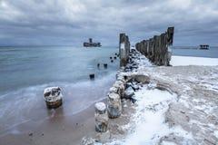 Замороженные деревянные волнорезы выравниваются к платформе торпедо Второй Мировой Войны на Балтийском море Стоковые Фото
