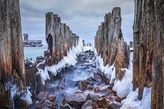 Замороженные деревянные волнорезы выравниваются к платформе торпедо Второй Мировой Войны на Балтийском море Стоковое Изображение