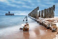 Замороженные деревянные волнорезы выравниваются к платформе торпедо Второй Мировой Войны на Балтийском море Стоковое Изображение RF