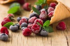 Замороженные поленики в конусе waffle, свежие вишни ягод голубик на старом деревянном столе - взгляде правильной позиции Стоковое фото RF