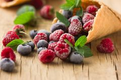 Замороженные поленики в конусе waffle, свежие вишни ягод голубик на старом деревянном столе - взгляде правильной позиции Стоковое Изображение RF