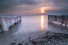 Замороженные пристани в море на заходе солнца Стоковые Фотографии RF
