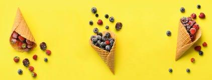 Замороженные ягоды - клубника, голубика, ежевика, поленика в конусах waffle на желтой предпосылке Взгляд сверху знамена стоковые изображения