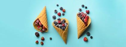 Замороженные ягоды - клубника, голубика, ежевика, поленика в конусах waffle на голубой предпосылке Взгляд сверху знамена стоковое фото