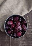 Замороженные ягоды смешивают в малом стальном ведре на деревянном столе Стоковое Фото