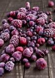 Замороженные ягоды смешивают в малом стальном ведре на деревянном столе Стоковая Фотография