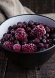 Замороженные ягоды смешивают в черном шаре на деревянной предпосылке Стоковые Изображения RF