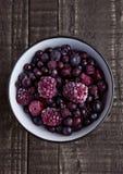 Замороженные ягоды смешивают в черном шаре на деревянной предпосылке Стоковая Фотография RF
