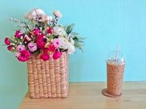 Замороженный кофе в пластичных чашке и цветках в корзине на деревянной таблице Стоковые Изображения RF