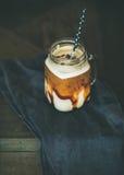 Замороженный кофе macciato карамельки с молоком в стеклянном опарнике стоковые изображения