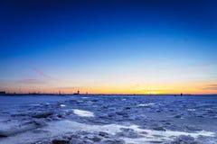 Замороженный океан на заходе солнца - заходе солнца Балтийского моря на пляже в Таллине, Эстонии Стоковое фото RF