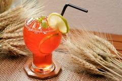 Замороженный чай лимона с украшением известки и мяты на предпосылке деревянных и хлопьев - мягком фокусе Стоковое фото RF