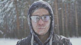 Замороженный человек с стеклами в снеге смотрит камеру в лесе зимы после шторма снега Стоковое фото RF