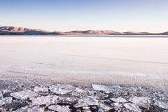 Заморозьте и идите снег на озере на заходе солнца стоковое изображение rf