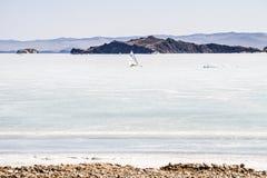 Заморозьте конкуренции гребли в зиме на Lake Baikal в ясной погоде в горах и изваяйте от снега в форме таблицы Стоковые Изображения