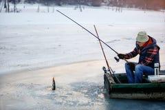 Заморозьте рыбную ловлю на замороженной рыбной ловле рыболова озера на льде стоковая фотография