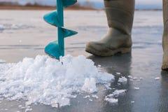 Заморозьте сверлить на рыбной ловле зимы, старом сверле и сломленном льде стоковая фотография