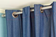 Занавесы джинсовой ткани с вершин кольц рельсом Стоковое фото RF