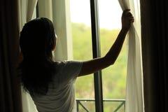 Занавесы отверстия женщины в спальне Стоковая Фотография