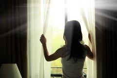 Занавесы отверстия женщины в спальне Стоковые Изображения RF