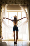 Занавесы отверстия молодой женщины в спальне на гостиничном номере раньше пойти outdoors Стоковое Изображение