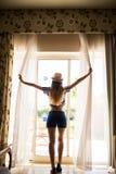 Занавесы отверстия молодой женщины в спальне на гостиничном номере раньше пойти outdoors Стоковая Фотография