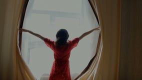 Занавесы отверстия молодой женщины в спальне сток-видео