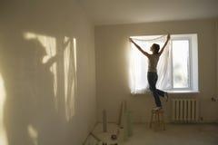 Занавес женщины подходящий в новой квартире стоковая фотография rf