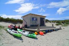Заниматься серфингом лачуга и каноэ на пляже песка стоковое фото rf