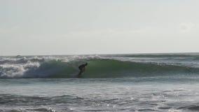 Занимающся серфингом в острове Бали океана, Индонезия Серферы занимаясь серфингом на surfboard на голубых волнах моря