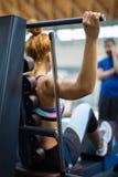 Занимаясь культуризмом и здоровая концепция образа жизни: Девушка имея разминку с тренажером в спортзале Стоковая Фотография RF