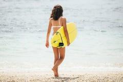 Занимаясь серфингом девушка женщины серфера идя держащ surfboard Принципиальная схема перемещения летних каникулов водных видов с Стоковая Фотография RF