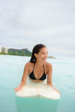 Занимаясь серфингом девушка серфера ища прибой на surfboard Стоковое Изображение