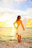 Занимаясь серфингом девушка серфера смотря океан приставает заход солнца к берегу Стоковая Фотография