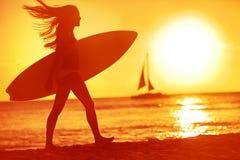 Занимаясь серфингом малыш женщины серфера приставает потеху к берегу на заходе солнца Стоковые Фото